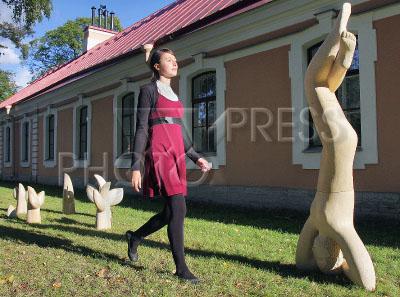 2369639 / Выставка `Кариатида - женщина, несущая мир`. Выставка ландшафтной скульптуры Веры Виглиной `Кариатида - женщина, несущая мир`. Девушка идет по газону мимо скульптуры `Кариатида`.