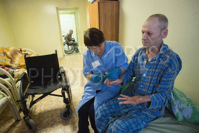 4179198 / Большекулачинский дом-интернат. БСУСО `Большекулачинский специальный дом-интернат для престарелых и инвалидов`. На снимке: медицинский персонал и пожилой мужчина.