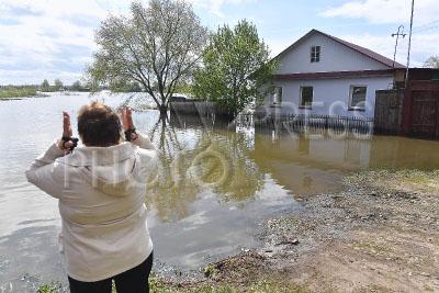 4213240 / Весенний паводок. Весенний паводок. На снимке: местная жительница у подтопленного частного дома.