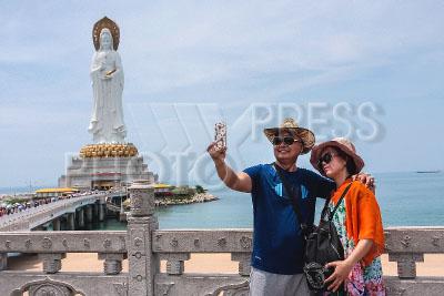 4238427 / Статуя богини Гуаньинь. Центр буддизма Наньшань. Парк культуры Гуаньинь. На снимке: 108 метровая статуя Богини Гуаньинь и туристы, делающие селфи.