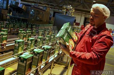 4266971 / Завод Coca-Cola. Завод Coca-Cola. Линия по производству соков под брендом `Добрый`. Сотрудник с пакетами сока в руках.