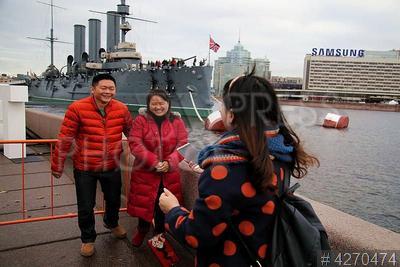 4270474 / Китайские туристы. `Красный маршрут`, посвященный 100-летию революции. Молодые китайцы на экскурсии фотографируются на фоне крейсера `Аврора`.