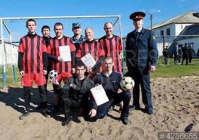 4286665 / Футбол в колонии. Исправительная колония №5. Футбольный матч. Команда-победитель с кубком и сотрудник ФСИН.
