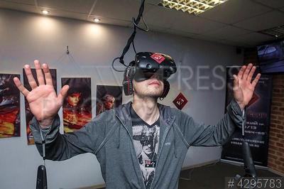 4295783 / Клуб виртуальной реальности. Клуб виртуальной реальности VRGameClub. Человек играет в шлеме виртуальной реальности играет в игру Cyber.
