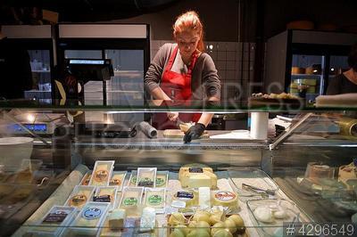 4296549 / Продажа сыров. Торговый центр `Центральный рынок`. Продавщица за прилавком с сырами.