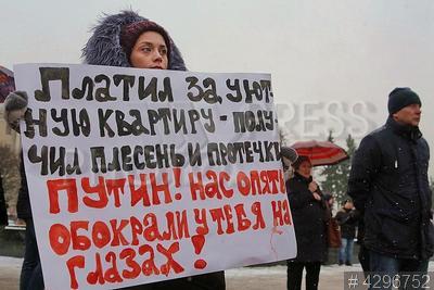 4296752 / Митинг обманутых дольщиков. Обманутые дольщики на митинге с плакатом `Платил за уютную квартиру - получил плесень и протечки. Путин! нас опять обокрали у тебя на глазах!`.