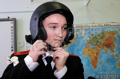4327921 / Кадет. Ярмарка военных профессий `Профессия настоящих мужчин`. Кадет надевает защитный шлем.