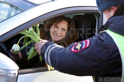4338359 / Акция `Цветы для автоледи`. Ежегодная акция ГИБДД `Цветы для автоледи`. Сотрудник ДПС поздравляет женщину-водителя с наступающим праздником 8 марта.