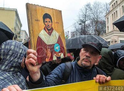 4372449 / Первомай. Первомайская демонстрация. Мужчина несет плакат в виде иконы с портретом Павла Дурова и значком `Телеграм` в колонне оппозиции.