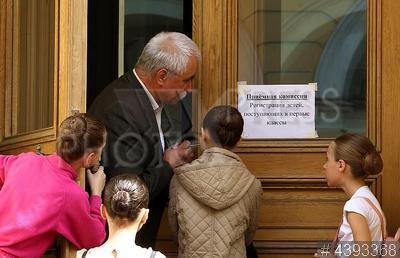 4393368 / `Приемная комиссия`. Поступление в Академию русского балета имени А.Я. Вагановой. Девочки у двери с объявлением `Приемная комиссия. Регистрация детей, поступающих в первые классы`.