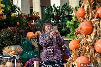 4441119 / Фестиваль `Золотая осень`. Гастрономический фестиваль `Золотая осень 2018`. Посетительница фотографирует художественную композицию из тыкв.