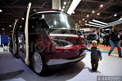 4449995 / Беспилотный автобус. 2-й Международный автобусный салон Busworld Russia. Мальчик стоит у беспилотного автобуса КамАЗ-1221 `ШАТЛ`.