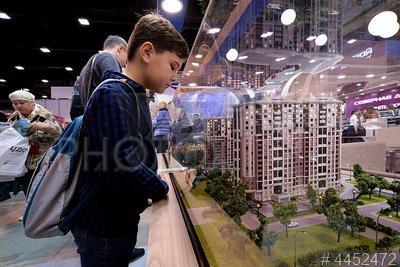 4452472 / Выставка `Ярмарка недвижимости`. Выставка `Ярмарка недвижимости 2018`. Мальчик рассматривает макет новостройки.