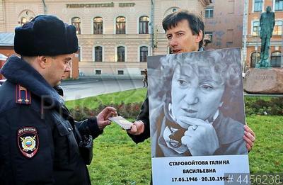 4456238 / `Прогулка` против ненависти. `Прогулка` против ненависти памяти Николая Гиренко. Сотрудник полиции и участник акции с портретом российского политика Галины Старовойтовой, убитой в 1998 году.