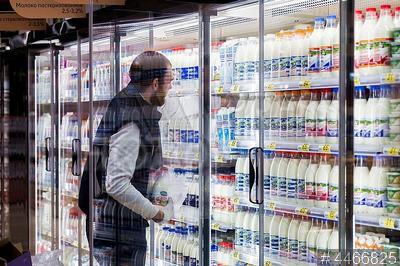 4466825 / Покупатель в магазине. Магазин новой концепции сети `Ашан`. Покупатель выбирает молоко.