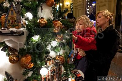 4467275 / Новогодняя елка. ГУМ. Выставка `Новогодние елки в ГУМе на Красной площади`. Ребенок на руках у мамы рассматривает игрушки на новогодней елке.