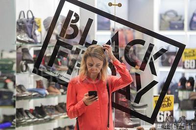 4467511 / `Черная пятница`. ТРЦ `Галерея`. Торговая акция `Черная пятница` (Black Friday). Девушка с мобильным телефоном у витрины обувного магазина.