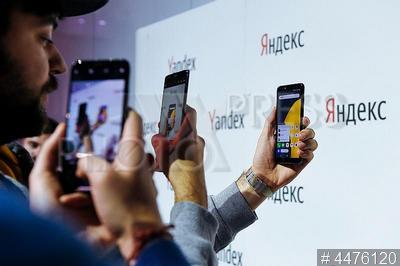 4476120 / `Яндекс.Телефон`. Презентация первого смартфона от `Яндекс`. Люди фотографируют `Яндекс.Телефон`.