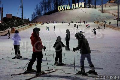 4489340 / Горные лыжи. Зимний отдых. Всесезонный курорт `Охта парк`. Горнолыжный склон. Взрослые и дети катаются на горных лыжах.