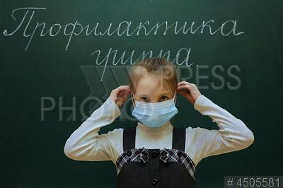 4505581 / Урок здоровья. Урок по профилактике гриппа. Школа №486. Школьница в медицинской маске у доски с надписью `Профилактика гриппа`.