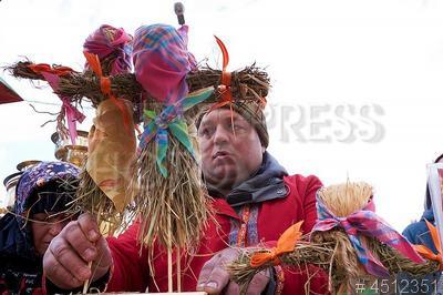 4512351 / Масленица. `Коломенское`. Празднование Масленицы. Масленичные гуляния. Мужчина с соломенными куклами Масленицы.