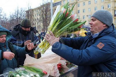 4512478 / Покупка тюльпанов. Подготовка к 8 марта. Предпраздничная торговля. Уличная продажа цветов. Мужчина покупает тюльпаны.