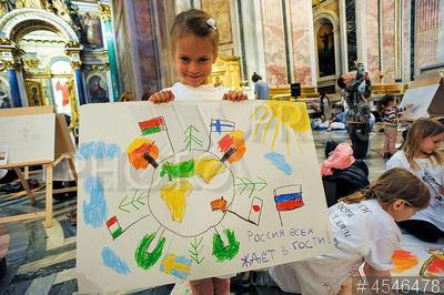 4546478 / Акция `Дети рисуют в храме`. 12-я ежегодная акция `Дети рисуют в храме` на тему `Все флаги в гости будут к нам`. Девочка с рисунком с надписью `Россия всех ждет в гости!`.
