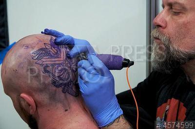 4574599 / Тату конвенция. 10-я Международная московская тату конвенция (ММТК). Мастер наносит татуировку.