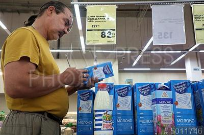5011746 / Покупатель в магазине. Продажа молочных продуктов с 1 июля по новым правилам. Супермаркет `Карусель`. Отдел молочной продукции. Мужчина читает состав молока на этикетке.