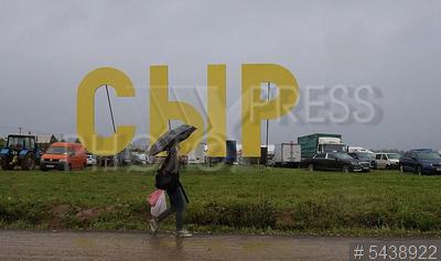 5438922 / Фестиваль сыра. 4-й Всероссийский фестиваль фермерской продукции `Сыр. Пир. Мир`. Посетительница под зонтом на фоне слова `Сыр`.