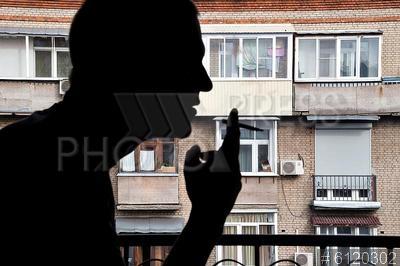 6120302 / Курение на балконе. Молодой человек курит на балконе жилого дома.