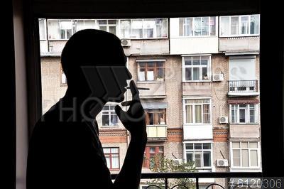 6120306 / Курение на балконе. Молодой человек курит на балконе жилого дома.