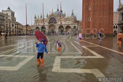 6138928 / Наводнение в Венеции. Наводнение в Венеции. Дети в полиэтиленовых бахилах гуляют под дождем на залитой водой площади Святого Марка.