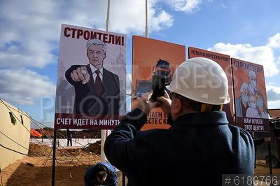 6180766 / Агитационный плакат. Пандемия коронавируса COVID-19 в Москве. Строительство инфекционной больницы на 500 мест для зараженных коронавирусом. Мужчина фотографирует гаджетом агитационный плакат с изображением мэра Москвы Сергея Собянина и надписью `Строители! Счет идет на минуты`.