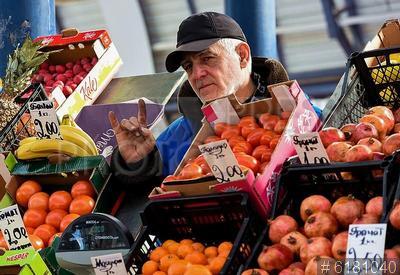 6181040 / Продажа овощей и фруктов. Комаровский рынок. Продажа овощей и фруктов. Продавец за прилавком.