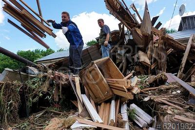 6201982 / Последствия прорыва дамбы. Устранение последствий прорыва дамбы на Озернинском водохранилище. Рабочие разбирают завалы дома, который снесло водным потоком.