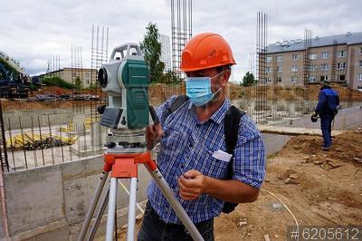 6205612 / Измерительные работы. Поселок Тучково. Строительство новой школы. Прораб в защитной маске производит измерительные работы.