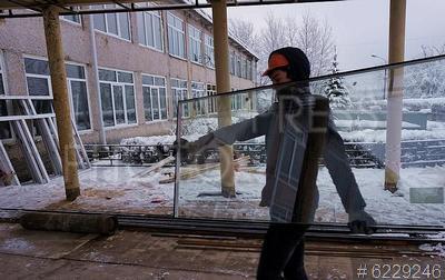 6229246 / Ремонт школы. Ремонт сельской школы. Средняя общеобразовательная школа. Рабочий несет оконное стекло.