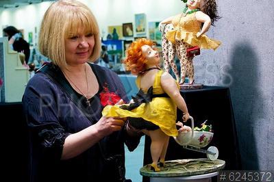 6245372 / Выставка `Искусство куклы`. 11-я Московская международная выставка `Искусство куклы`. Женщина около выставочного стенда.
