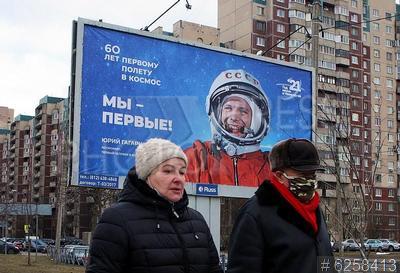 6258413 / Социальная реклама. Рекламная тумба с изображением космонавта Юрия Гагарина, посвященная 60-летию первого полета человека в космос. Пара в защитных масках.