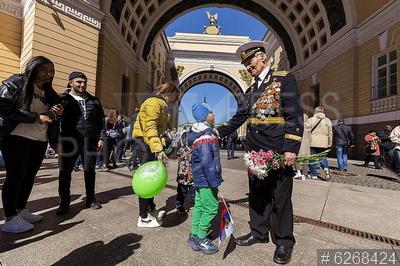 6268424 / День Победы. Празднование 76-й годовщины Победы в Великой Отечественной войне. Ветеран войны с цветами и ребенок.