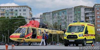 6270065 / Медицинский вертолёт. Бригада скорой помощи грузится в медицинский вертолёт `АНСАТ`.