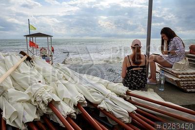 6283450 / Люди на пляже. Шторм в Сочи. Люди сидят на пляже Адлерского района.