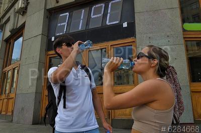 6284668 / Жара в Москве. Молодые люди пьют минеральную воду на фоне градусника Центрального телеграфа, показывающего температуру воздуха +31.