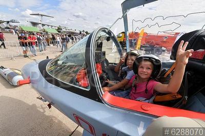 6288070 / Авиасалон `МАКС-2021`. 15-й Международный авиационно-космический салон `МАКС-2021`. Дети сидят в кабине военного самолета.