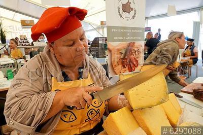 6290088 / Фестиваль сыра. Всероссийский гастрономический фестиваль `Сыр. Пир. Мир`. Продавщица нарезает сыр.